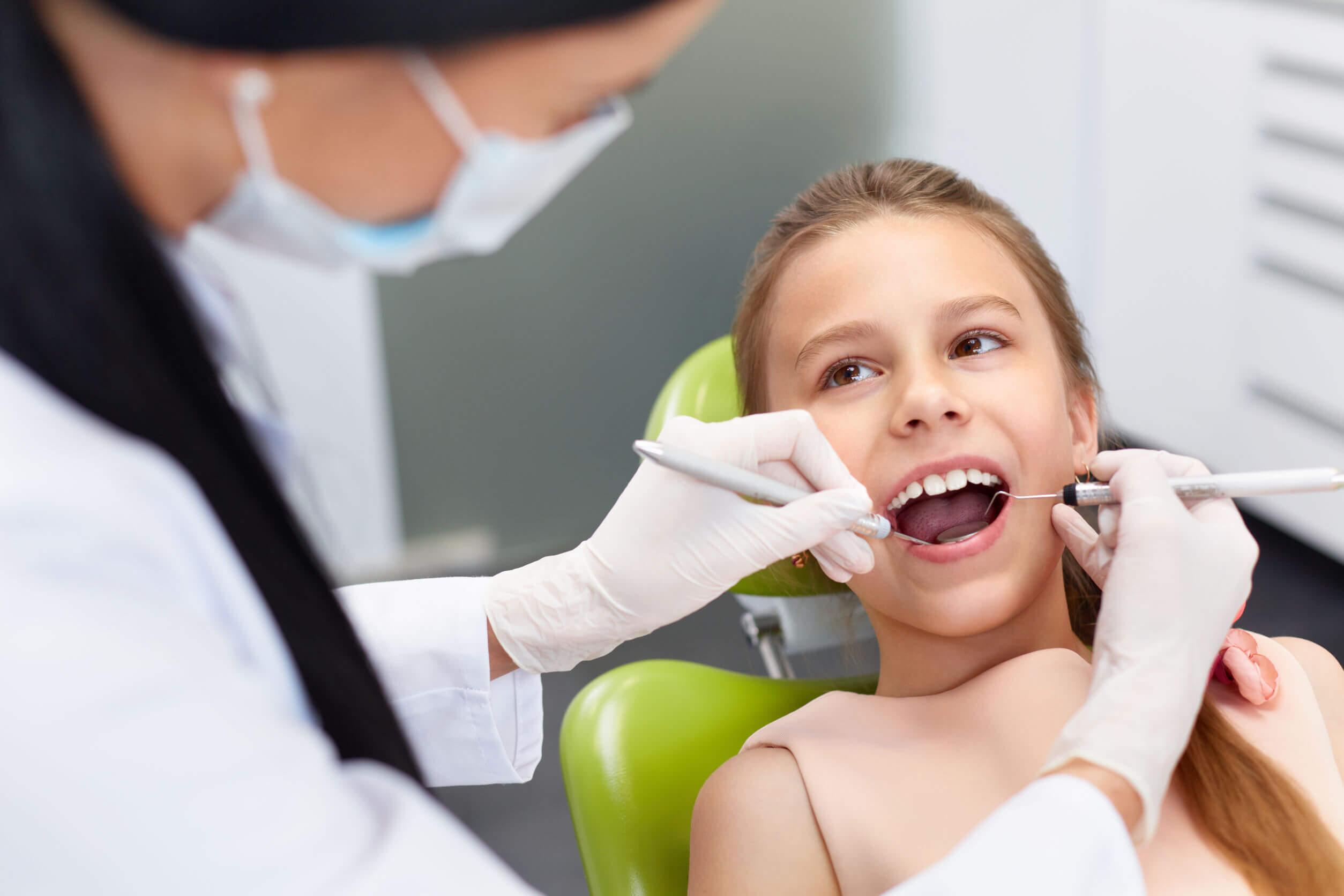 odontólogo pediatra haciendo limpieza dental a niño